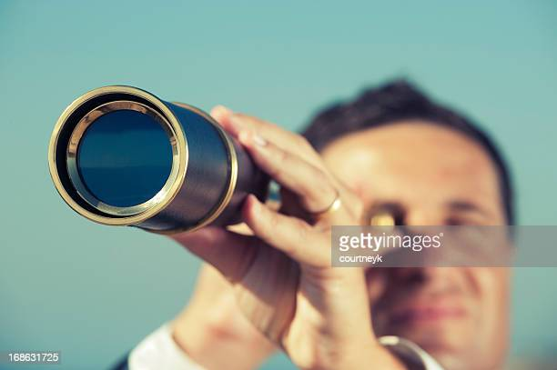 The way forward. Businessman looking through a telescope