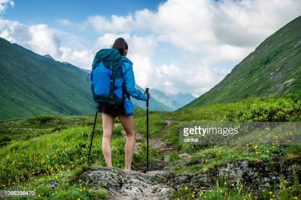 the way forward. woman traveler in the mountains. - caucasus stock pictures, royalty-free photos & images