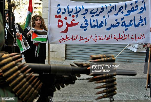 The weapon of a soldier standing guard is seen as protestors hold a banner that reads in Arabic 'Stop the war crimes and the genocide against our...
