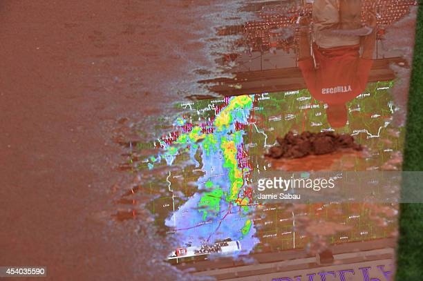 The weather radar being shown on the scoreboard at Great American Ball Park is reflected in a large puddle on the field during a rain delay before a...