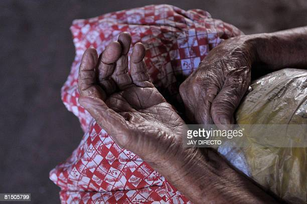 The weathered hands of eightytwo yearold Benita Santos are seen as she begs in her usual spot in Manila on June 8 hoping to beg enough money to...