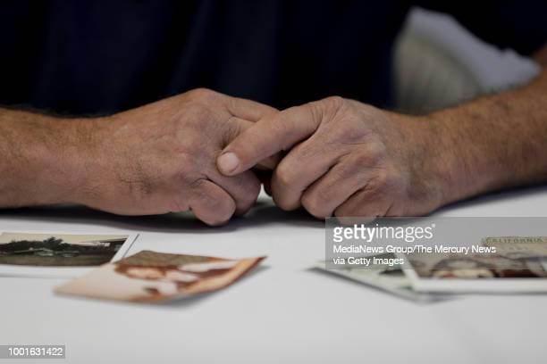 The weathered hands of Victor Hayes a survivor of the East Area Rapist photographed with old pictures of himself in the foreground during an...