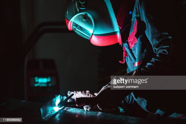 the welding male welder working in the workshop - fabricage apparatuur stock pictures, royalty-free photos & images