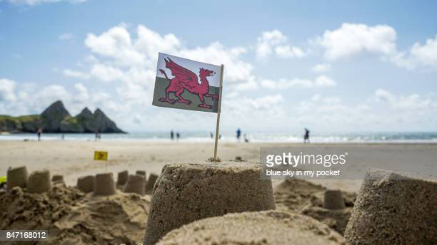 the welsh flag on a sand castle at the beach. - welsh flag stock pictures, royalty-free photos & images