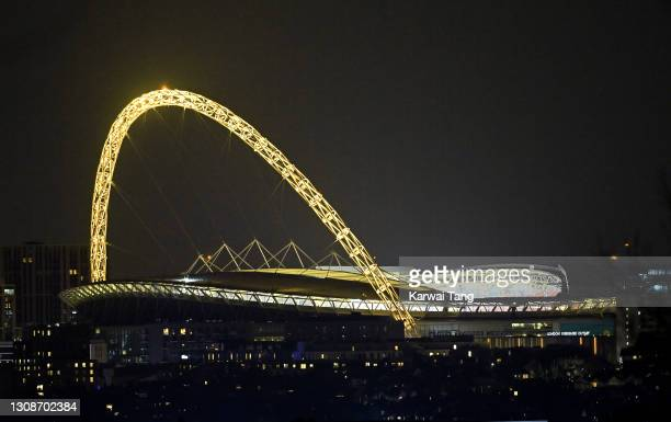 The Wembley Stadium arch is lit up yellow to mark the National Day of Reflection for the Covid Dead on March 23, 2021 in London, England. Marie Curie...