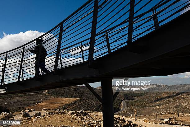 The West Bank Jewish settlement of Eli is seen in the background as a silhouetted Israeli child is seen visiting the archaeological park of Ancient...
