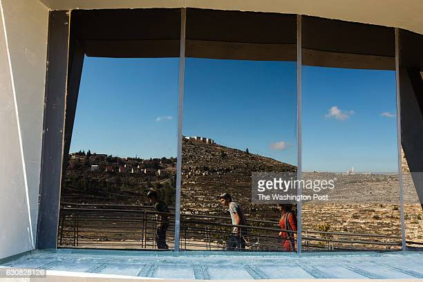 The West Bank Jewish settlement of Shiloh a nearby Palestinian village and Israeli visitors are reflected in the windows of the lookout tower at the...