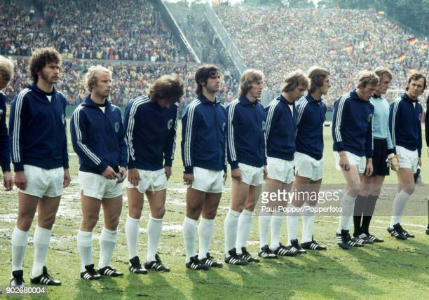 The West German team line up for the National Anthems prior to the FIFA World Cup match between Poland and West Germany at the Waldstadion in...