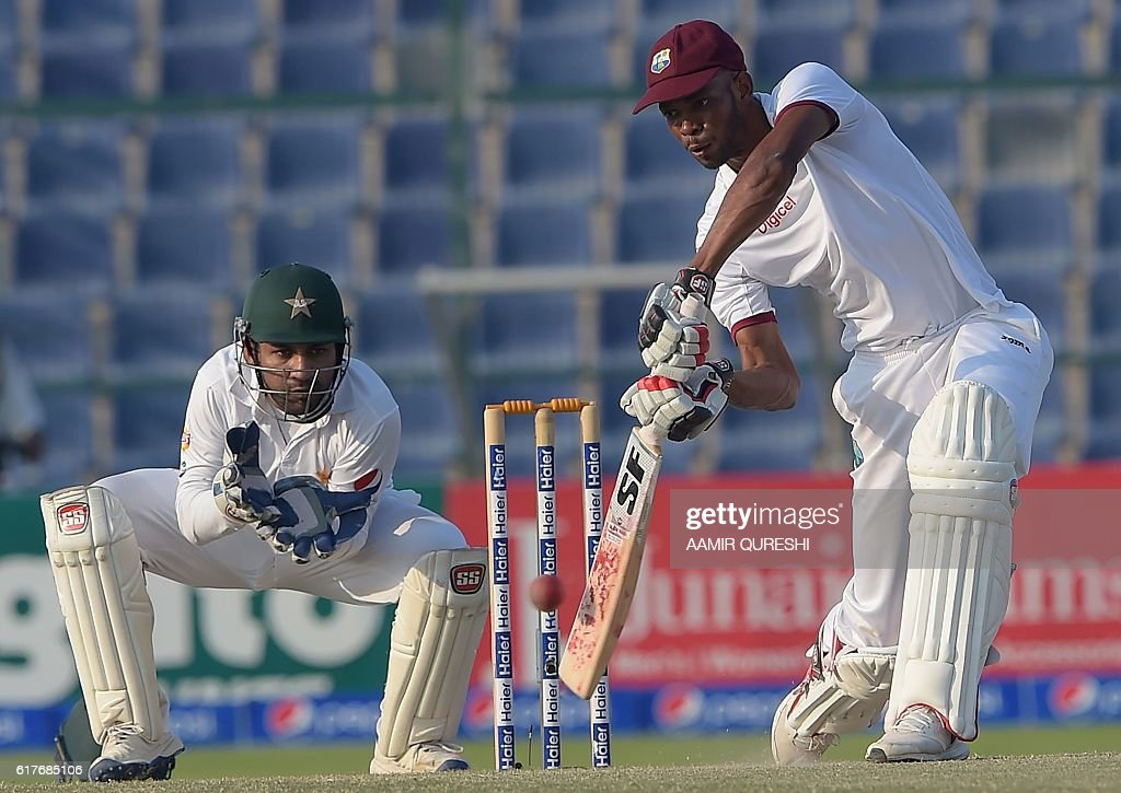 The West Indies' batsman Roston Chase (R) plays a shot as Pakistani wicketkeeper Sarfraz Ahmed looks on during the fourth day of the second Test between Pakistan and the West Indies at the Sheikh Zayed Cricket Stadium in Abu Dhabi on October 24, 2016. Pakistan pressed West Indies hard for a series-clinching win in the second Test after setting a daunting 456-run target on the fourth day in Abu Dhabi. By close of play Pakistan had taken four wickets at 171 leaving the West Indies to bat out the fifth and final day on October 25 or score a further 285 runs with six wickets intact for an unlikely win. / AFP / AAMIR