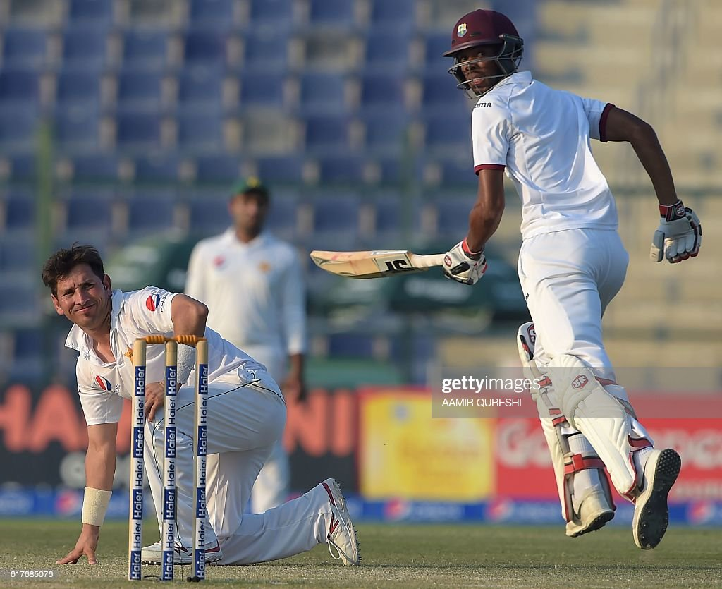 The West Indies' batsman Roston Chase (R) runs past Pakistani spinner Yasir Shah (L) on the fourth day of the second Test between Pakistan and the West Indies at the Sheikh Zayed Cricket Stadium in Abu Dhabi on October 24, 2016. Pakistan pressed West Indies hard for a series-clinching win in the second Test after setting a daunting 456-run target on the fourth day in Abu Dhabi. By close of play Pakistan had taken four wickets at 171 leaving the West Indies to bat out the fifth and final day on October 25 or score a further 285 runs with six wickets intact for an unlikely win. / AFP / AAMIR