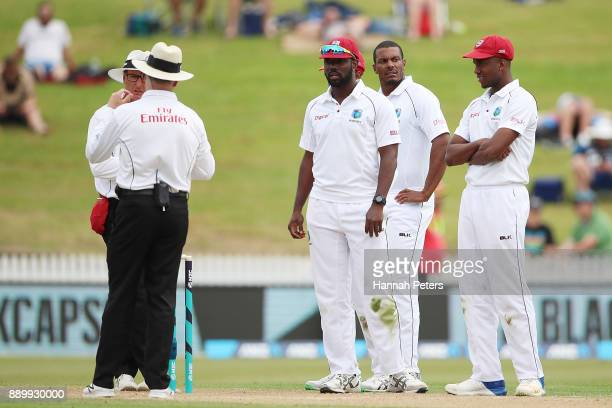 The West Indies wait for the third umpire to rule on a lbw decision for the wickte of Colin de Grandhomme of New Zealand during day three of the...