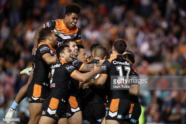 The West Tigers players celebrate with Tuimoala Lolohea of the Tigers after he scored a try during the round 23 NRL match between the Wests Tigers...
