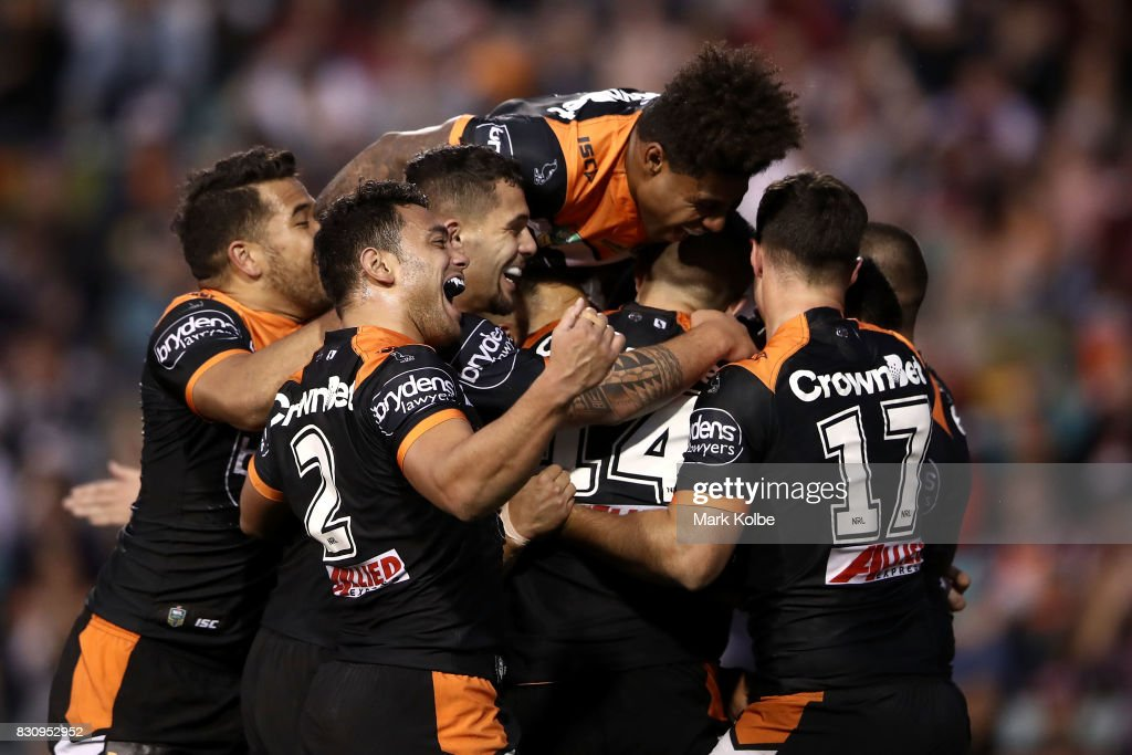 The West Tigers players celebrate with Tuimoala Lolohea of the Tigers after he scored a try during the round 23 NRL match between the Wests Tigers and the Manly Sea Eagles at Leichhardt Oval on August 13, 2017 in Sydney, Australia.