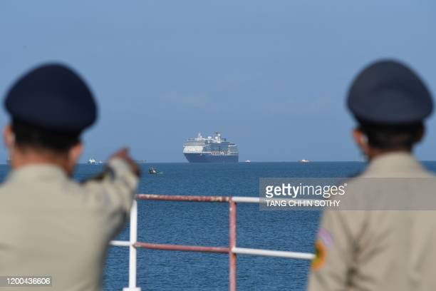 TOPSHOT The Westerdam cruise ship is seen past Cambodian policemen as it approaches port in Sihanoukville Cambodia's southern coast on February 13...