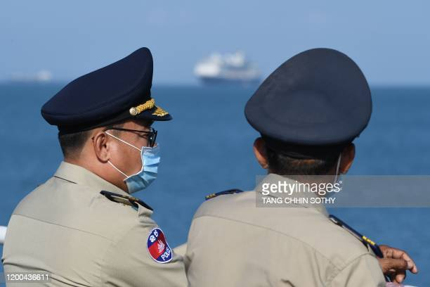 The Westerdam cruise ship is seen past Cambodian policemen in protective facemasks as it approaches port in Sihanoukville Cambodia's southern coast...