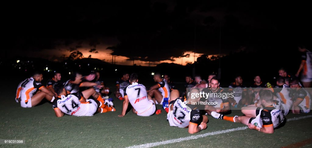The Wests Tigers team sit on the field during a power outage as lightning flashes in the background during the NRL trial match between the North Queensland Cowboys and the Wests Tigers at Barlow Park on February 17, 2018 in Cairns, Australia.