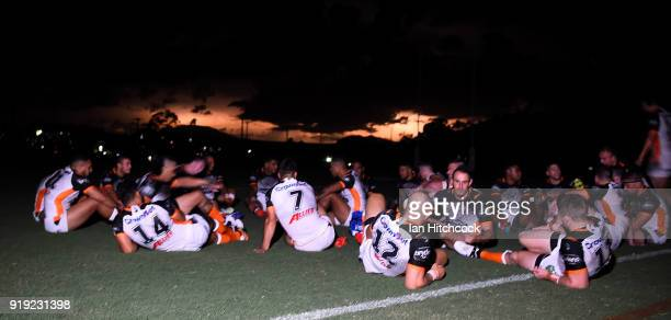 The Wests Tigers team sit on the field during a power outage as lightning flashes in the background during the NRL trial match between the North...