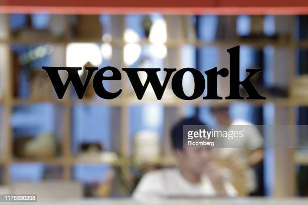 The WeWork logo sits on display on a glass door of the entrance to the WeWork Ocean Gate Minatomirai co-working office space, operated by The We...