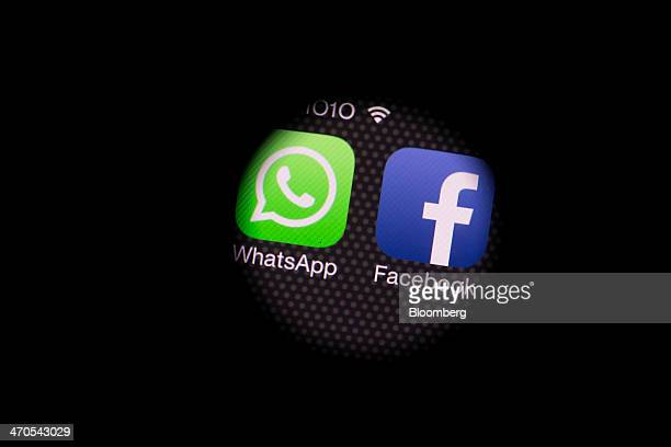 The WhatsApp Inc mobilemessaging application WhatsApp and the Facebook Inc application are see through a camera lens placed on top of an Apple Inc...