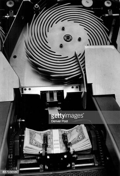 The wheel at the top is money spinning around at the bottom the good money drops out in piles of 100 bills the rest shots by to be gotten rid of...