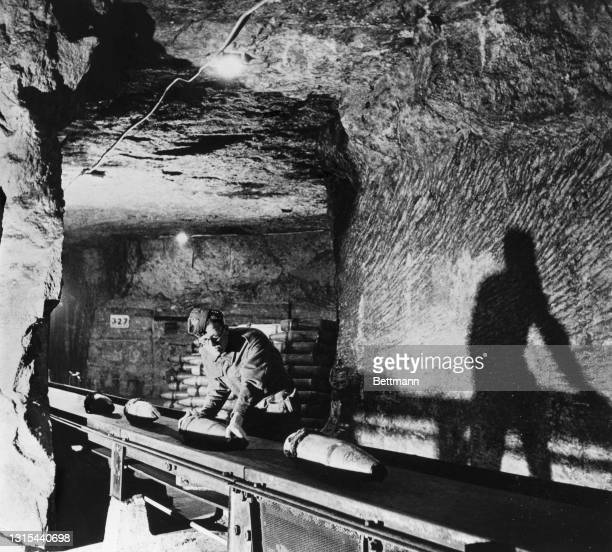 The white cliffs of Dover, celebrated in song and story, had their quota of cavern factories during he war. This belt conveyor for munitions...