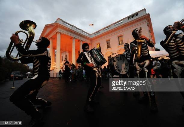 """The White House is lit with orange light as a group of """"skeletons"""" perform at the North Portico of the White House in Washington on October 31, 2009...."""