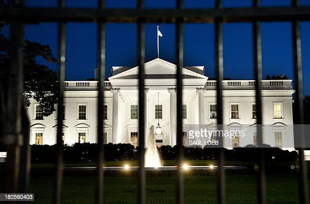 The White House is seen at dusk on the eve of a possible government shutdown as Congress battles out the budget in Washington, DC, September 30,...