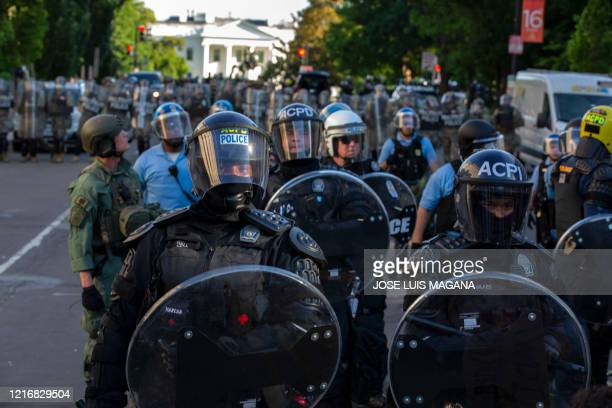 The White House is seen behind a line of police officers wearing riot gear as they push back demonstrators on June 1 2020 in Washington DC during a...