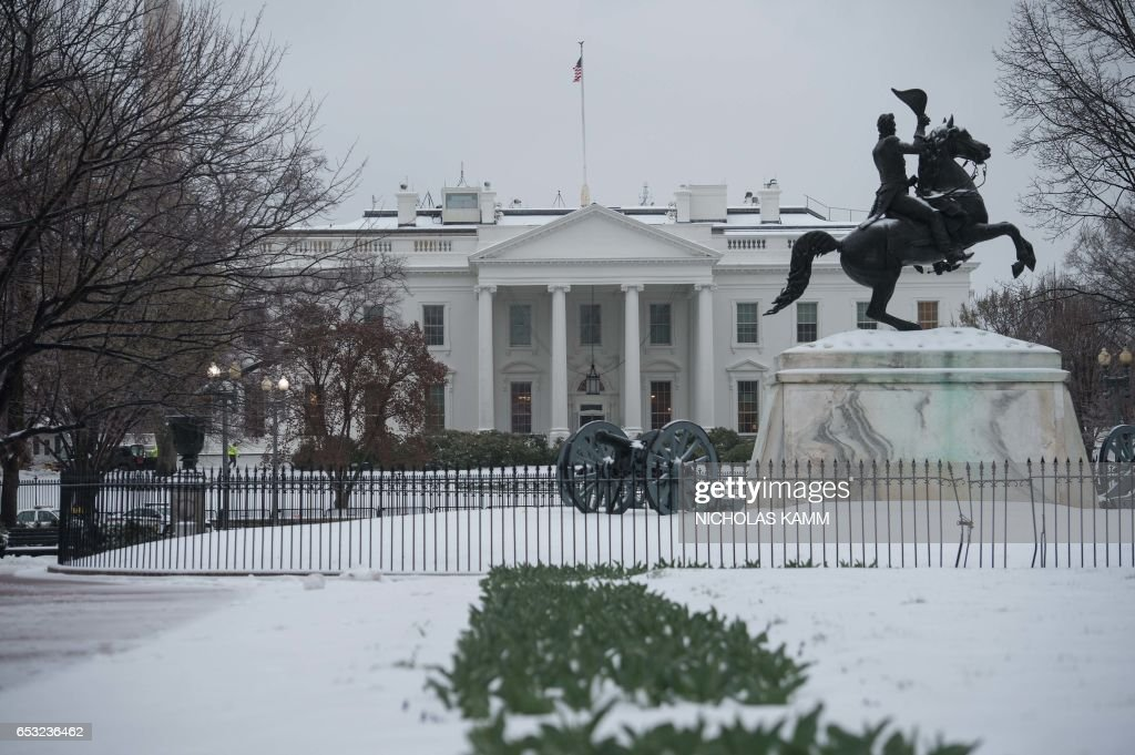 The White House is seen from Lafayette Square in Washington, DC, on March 14, 2017 following a snowstorm. Winter Storm Stella dumped snow and sleet Tuesday across the northeastern United States where thousands of flights were canceled and schools closed, but appeared less severe than initially forecast. KAMM