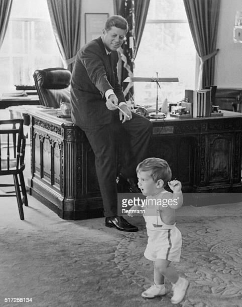 The White House released this picture showing President Kennedy watching his 18monthold son John Jr prancing about in the Chief Executive's office...