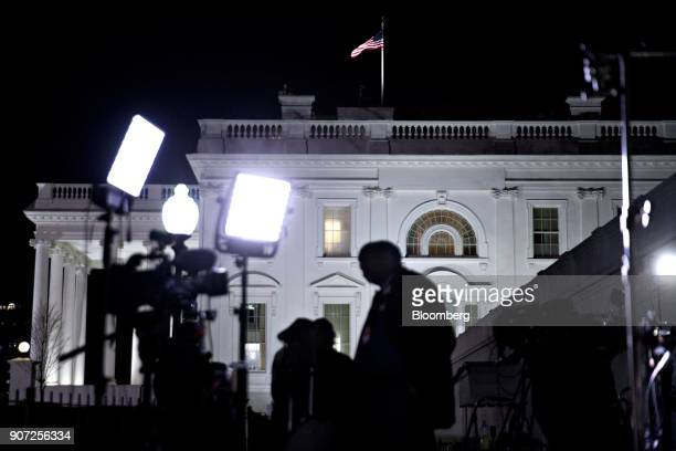 The White House stands past members of the media and television cameras in Washington DC US on Friday Jan 19 2018 Temporary government funding runs...