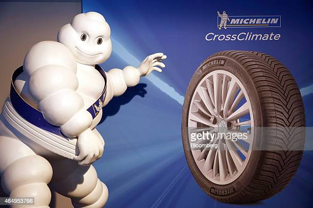The white Michelin Man mascot of Michelin Cie stands alongside a poster of the company's new CrossClimate automobile tire during their preshow event...