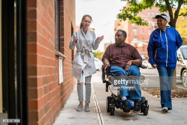 The White teenager girl talking with disabled wheel-chaired African American man and woman when they walking on the street together