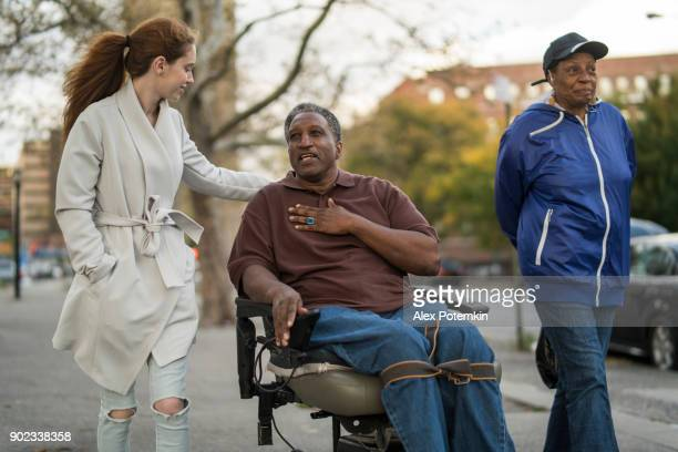the white teenager girl talking with disabled wheel-chaired african american man and woman when they walking on the street together - african american man helping elderly stock pictures, royalty-free photos & images