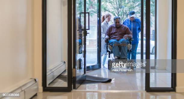 The White teenager girl talking with disabled wheel-chaired African American man and woman entering the residential living building