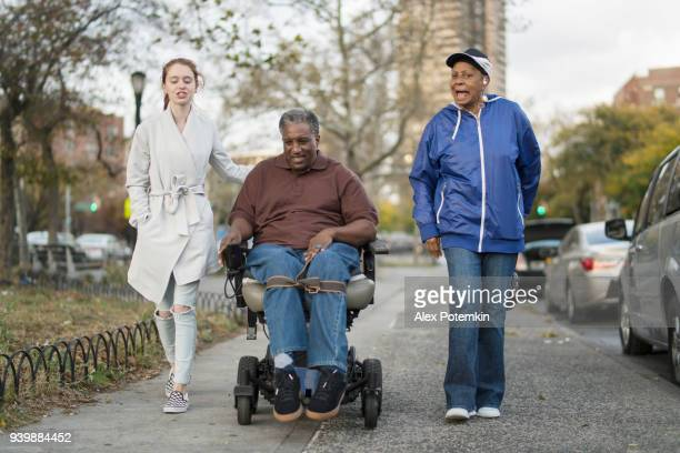the white teenager girl talking with disabled wheel-chaired african american man and woman when they walking on the street together - spinal cord injury stock photos and pictures