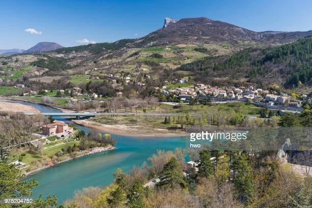 The whitewater river Buech flows into the Durance as right tributary, the district of Faubourg de la Baume and Montagne de Gache mountain with rocky promontory behind, Sisteron, Provence-Alpes-Cote d'Azur, France