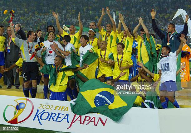 The whole Brazilian team celebrates on the pitch during the award ceremony at the International Stadium Yokohama Japan 30 June 2002 following...