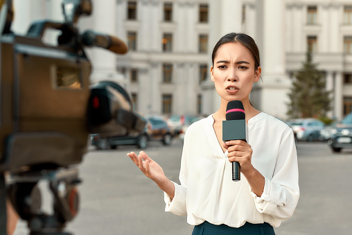 The whole truth and nothing but the truth. TV reporter presenting the news outdoors. Journalism industry, live streaming concept. 1187643614