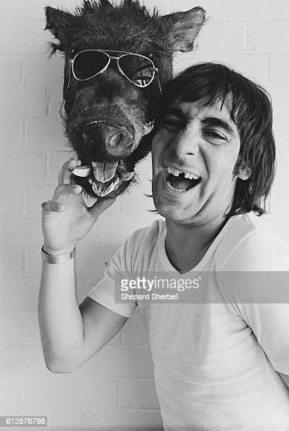 The Who's drummer Keith Moon touching a preserved warthog's head wearing aviator glasses