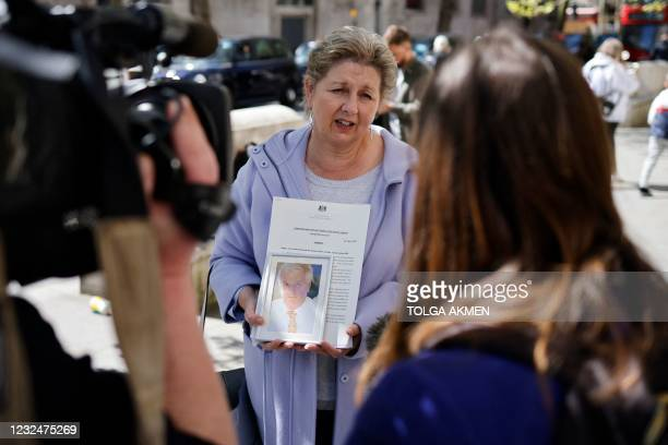 The widow of a former subpostmaster holds his photograph as she speaks to members of the media outside the Royal Courts of Justice in London, on...