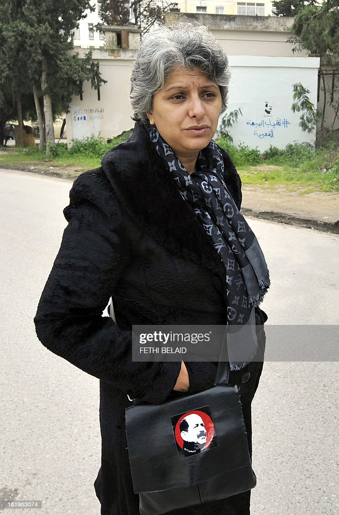The widow of murdered opposition figure Chokri Belaid (image on handbag), Besma Khalfaoui, arrives at the site of the vandalised and broken statue erected in his honour, on February 18, 2013, in Tunis. The memorial, installed as a work of contemporary art by Tunisian artists, was ripped off from its base and broken, and the flowers surrounding it were trampled and scattered. Belaid, a leftist leader and fierce critic of Tunisia's ruling Islamist-led government, was shot dead by a gunman as he left his home. is seen left.