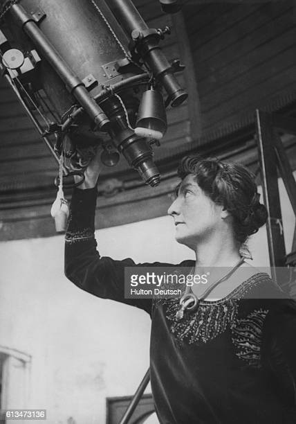 The widow of the French astronomer Camille Flammarion looks through the telescope in his observatory