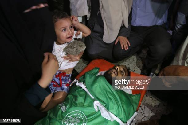 The wife and child of Mohammed Dwedar a 27 yearold Palestinian killed during clashes along the Gaza border the previous day attend his funeral in...