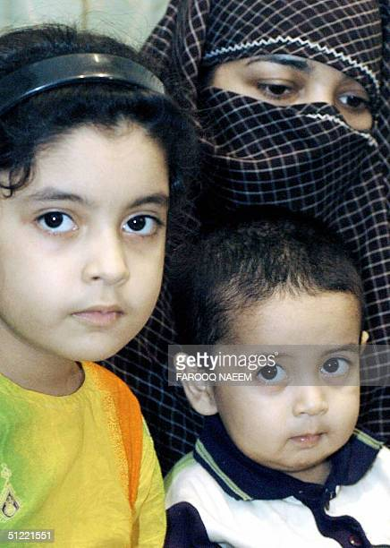 The wife and children of Pakistani Muslim cleric Abdul Rashid Ghazi look on during a press conference in Islamabad 26 August 2004 Ghazi is one of the...