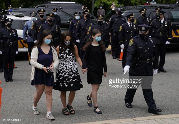 The wife and daughters of Charles Roberts follow as the pallbearers carry in the casket of Glen Ridge Police Officer Charles Rob Roberts who died of...