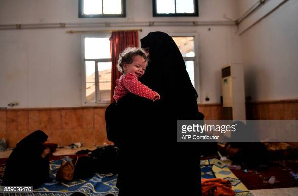 TOPSHOT The wife of a suspected member of the Islamic State group holds her child as she waits on the western frontline to be questioned after...