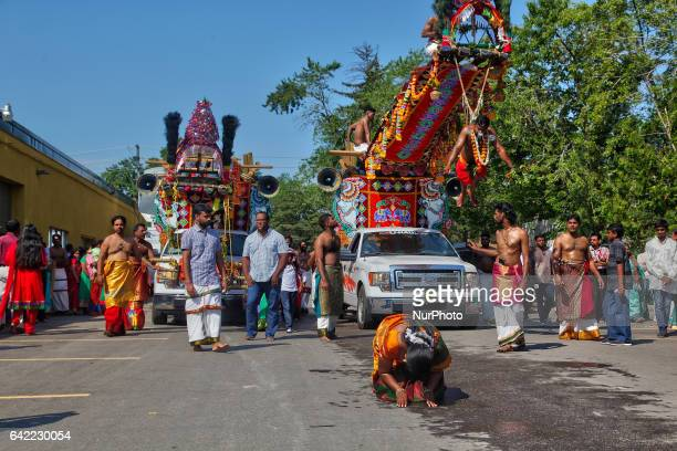The wife of a Tamil Hindu devotee performing the parakavadi ritual kneels in prayer on the pavement in front of her husband as he is suspended by...