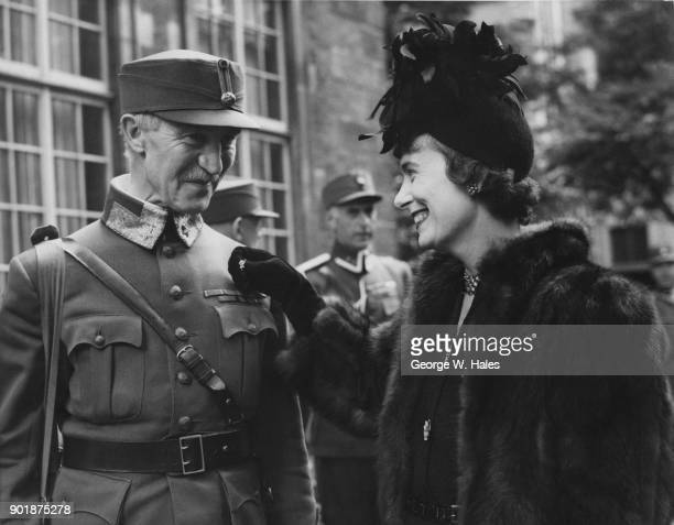 The wife of Anthony Joseph Drexel Biddle Jr the US Ambassador to Norway gives a pin to Carl Gustav Fleischer CommanderinChief of the Norwegian Forces...
