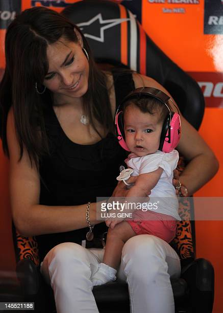 The wife of Australian rider Casey Stoner Adriana holds their daughter Alessandra Maria at the Catalunya racetrack in Montmelo near Barcelona on June...